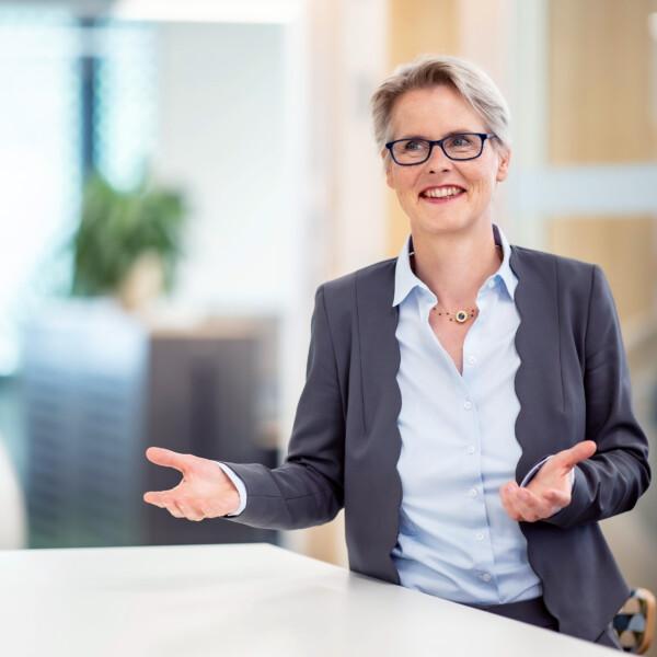 Birgit Frohnhoff, Vorständin steht an einem Tisch in einer Gesprächssituation.