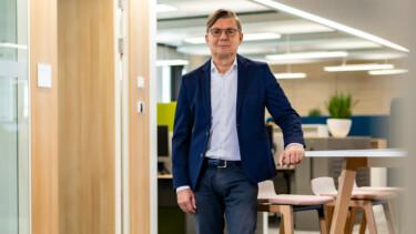 Jörg Staff steht an einem Bürotisch und blickt in die Kamera