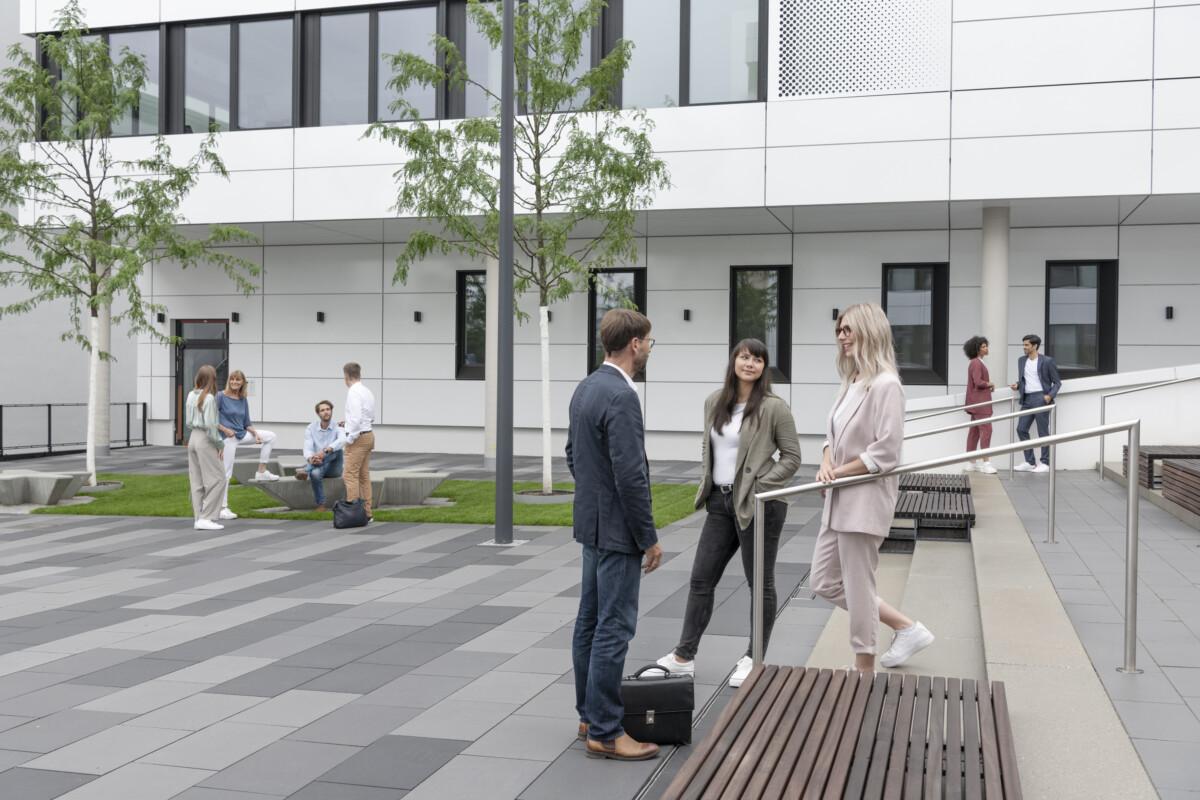 drei Personen unterhalten sich auf einem Campus im Freien