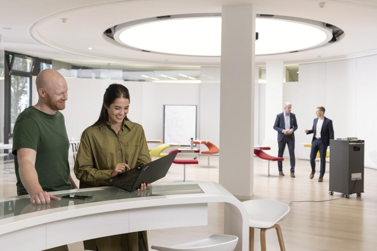 zwei Personen schauen sich etwas auf dem Laptop an, im Hintergrund laufen Kollegen
