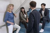 Vier Personen bei einem lockeren Gespräch im Treppenhaus