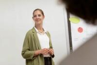 Eine junge Frau präsentiert bei einem Workshop ein Chartboard