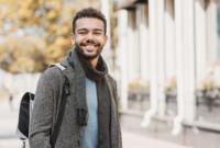 Ein junger Mann mit Rucksack lächelt in die Kamera.