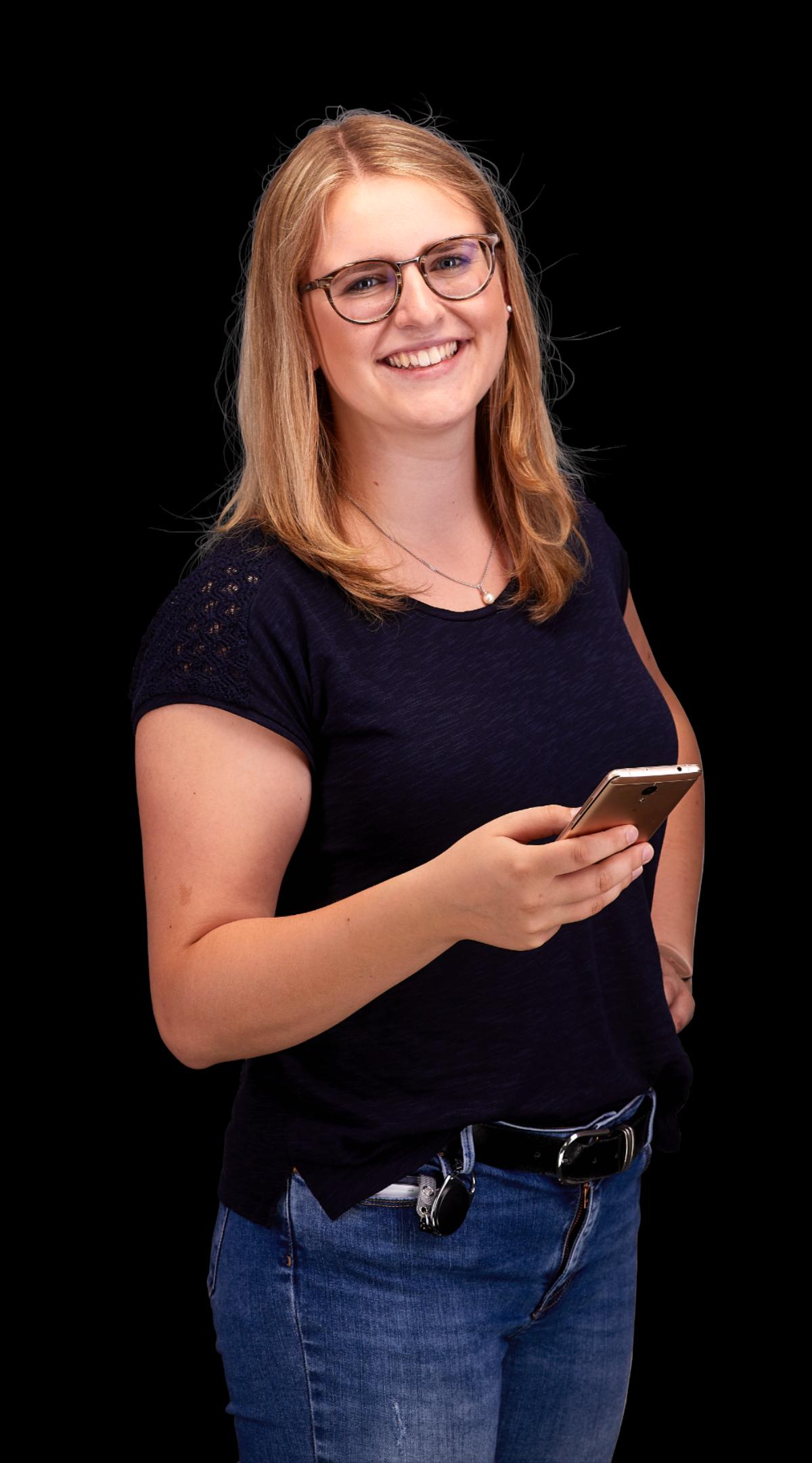 Portrait einer lächelnden jungen Frau, die ein Handy in der Hand hält.