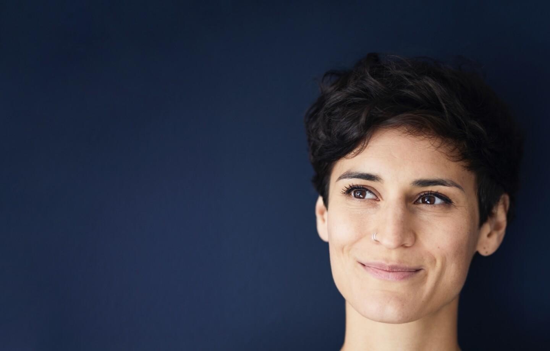 Portrait einer lächelnden Frau vor einer blauen Wand.