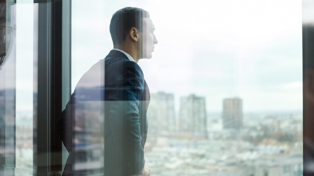 Geschäftsmann schaut von einem Bürobalkon hinaus. Das wird durch Glastüren fotografiert.